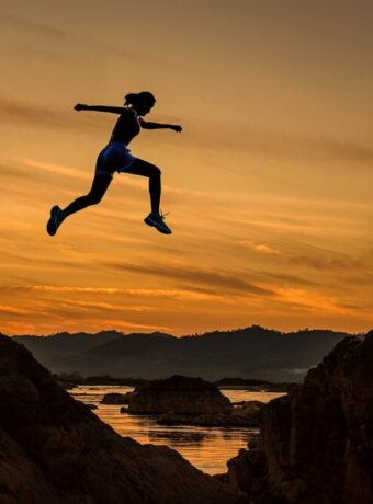 Woman Jumping Over a Rock